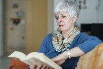 Ориентированная старшая женщина читает книгу дома — стоковое фото