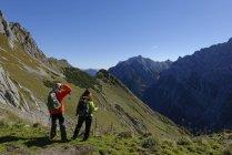 Austria, Tyrol, Karwendel, hikers looking at view at the Torscharte — Stock Photo