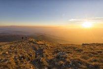 Itália, Marche, Monte San Vicino, dois caminhantes, olhando para a paisagem ao pôr do sol — Fotografia de Stock