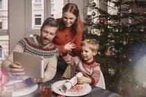 Família usando tablet digital na mesa de Natal decorada — Fotografia de Stock