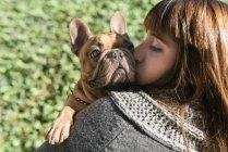 Портрет молодой женщины, целующейся с французским бульдогом — стоковое фото