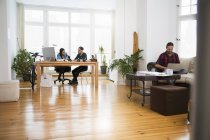 Three creative business people working in informal office — Stock Photo