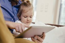 Father showing little daughter something on digital tablet — Stock Photo