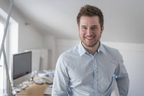 Портрет посміхаючись молода людина в офісі — стокове фото