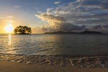 Seychelles, La Digue, Anse Source D'Argent, Île Praslin en arrière-plan, petite île aux arbres au coucher du soleil — Photo de stock