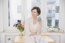 Smiling woman at home sitting on table holding cup — Stock Photo