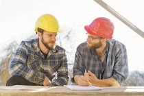 Craftsmen discussing and taking notes — Stock Photo