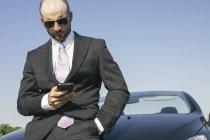 Geschäftsmann mit Sonnenbrille lehnt am Auto und schaut aufs Handy — Stockfoto
