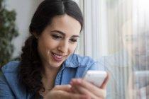 Lächelnde junge Frau schaut aufs Handy — Stockfoto