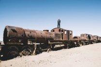 Bolivia, Uyuni treno cimitero, uomo nella cabina di un vecchio treno arrugginito — Foto stock