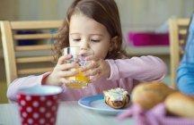 Portrait of little girl drinking glass of orange juice at breakfast table — Stock Photo