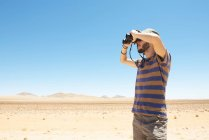 Namíbia, deserto de Namíbia, homem com chapéu usando binóculos para desviar o olhar — Fotografia de Stock