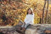 Retrato de la pequeña y feliz sentada sobre madera muerta en el bosque - foto de stock