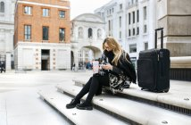 UK, London, young woman with luggage checking her cell phone on stairs — Stock Photo