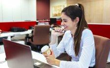 Усміхаючись Молодий підприємець з кави, щоб йти сидячи на її столі — стокове фото