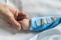 Visão cortada da mulher sênior e bebê de mãos dadas — Fotografia de Stock