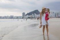 Brasil, Rio de Janeiro, mother carrying and kissing daughter on Copacabana beach — Stock Photo