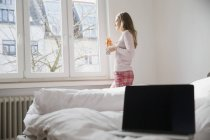 Young woman with croissant and cup of coffee standing in bedroom looking through window — Stock Photo