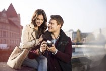 Германия, Берлин, молодая пара, смотрящая в камеру на берегу реки Шпрее — стоковое фото