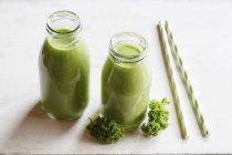 Две стеклянные бутылки капустного смузи с соломинками — стоковое фото