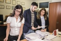 Three colleagues in office looking at documents — Stock Photo