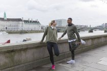 UK, London, two happy runners stretching at riverside — Stock Photo