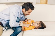 Playful father and son playing on sofa — Stock Photo