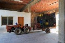 Трактор з стеки коробки на причепі — стокове фото