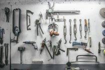 Ferramentas penduradas na parede de uma oficina — Fotografia de Stock