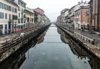Italy, Milan, Canal Naviglio Grande suroounded by buildings on shore — Stock Photo