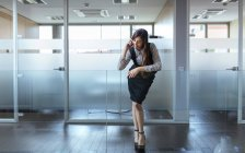 Businesswoman telephoning with smartphone at corridor of an office — Stock Photo