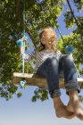 Smiling girl sitting on a swing in nature — Stock Photo
