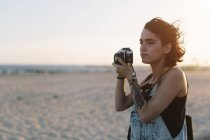 Young woman  taking photos on the beach at sunset — Stock Photo