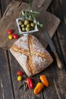 Ciabatta bread with green olives in bowl, tomatoes and mini capsicum on wood — Stock Photo