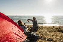 Giovane coppia da campeggio in riva al mare bere birra al tramonto — Foto stock