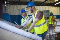 Строитель и инженер обсуждают проект в офисе на стройплощадке — стоковое фото