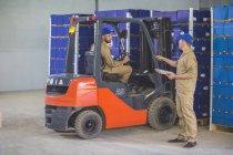 Trabalhador de meia carga com a empilhadeira na fazenda laranja — Fotografia de Stock
