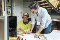 Мужские и женские архитекторов обсуждать работу в офисе — стоковое фото