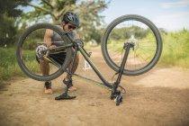 Молодой человек чинит горный велосипед во время велосипедного тура — стоковое фото