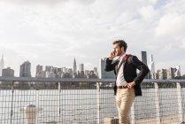 Бизнесмен на Ист-Ривер на сотовый телефон, Нью-Йорк, США — стоковое фото