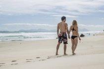 Молодая пара, идущая рука об руку на пляже — стоковое фото