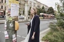 Femme dans la ville en tenant le téléphone cellulaire — Photo de stock
