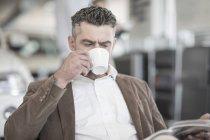 Homem bebendo café leitura revista no carro concessionária — Fotografia de Stock