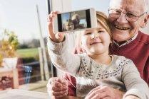 Дедушка и внучка делают селфи со смартфоном — стоковое фото