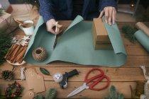Mujer de envolver los regalos de Navidad en la mesa con objetos decorativos - foto de stock