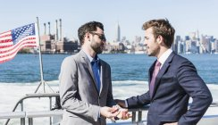 Two businessmen talking on ferry on East River, New York City, USA — Stock Photo