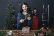 Молодая женщина режет веточку для украшения рождественского подарка — стоковое фото