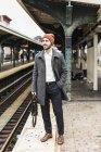 Jovem esperando na plataforma da estação de metro — Fotografia de Stock