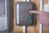 Cropped image of Hand turning off electrical control box — Stock Photo