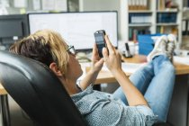 Woman reading messages on smartphone with feet on desk — Stock Photo